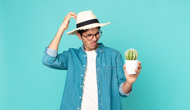 Young hispanic man feeling puzzled and confused, scratching head and holding a cactus