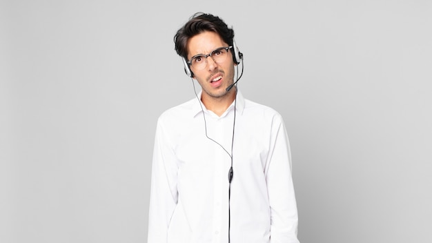 Young hispanic man feeling puzzled and confused. telemarketer concept