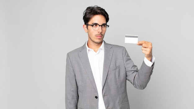 젊은 히스패닉 남자는 슬프거나 화가 나거나 화가 나서 옆을 바라보며 신용 카드를 들고 있습니다.