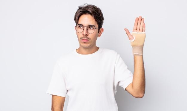 若いヒスパニック系の男性は、悲しみ、動揺、または怒りを感じ、横を向いています。手の包帯の概念