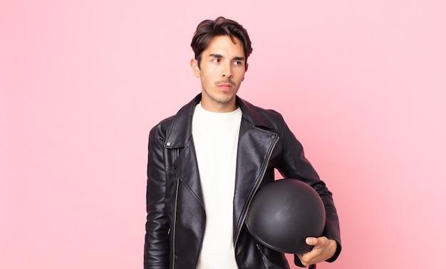 若いヒスパニック系の男性は、悲しみ、動揺、または怒りを感じ、横を向いています。バイクライダーのコンセプト