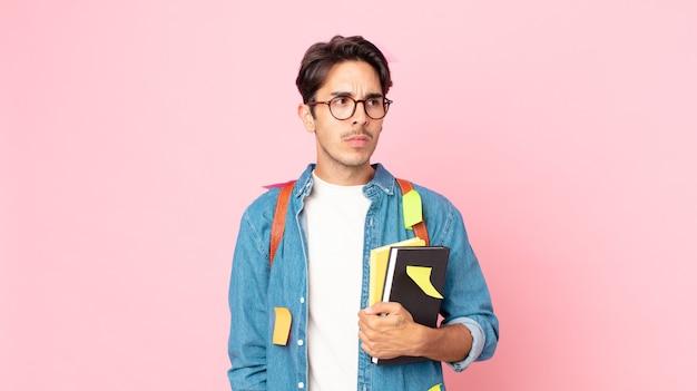 Молодой латиноамериканец грустит, расстроен или зол и смотрит в сторону. студенческая концепция