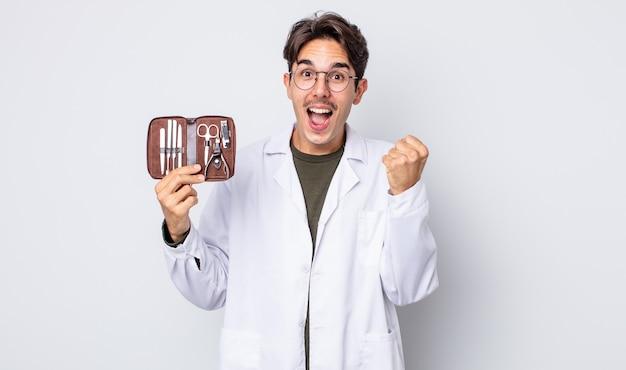 젊은 히스패닉 남자는 충격을 받고 웃고 성공을 축하합니다. 척추측만증 손톱 도구