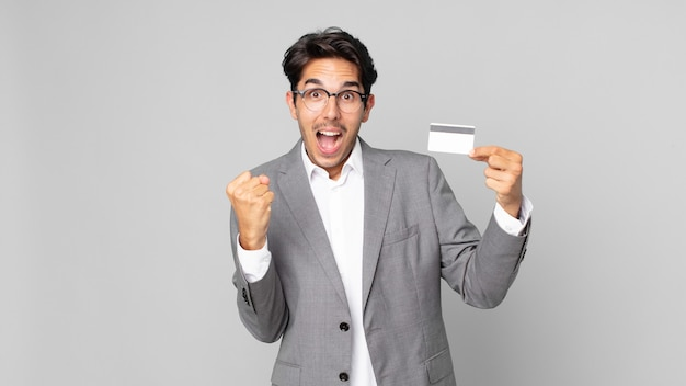Young hispanic man feeling shocked,laughing and celebrating success and holding a credit card