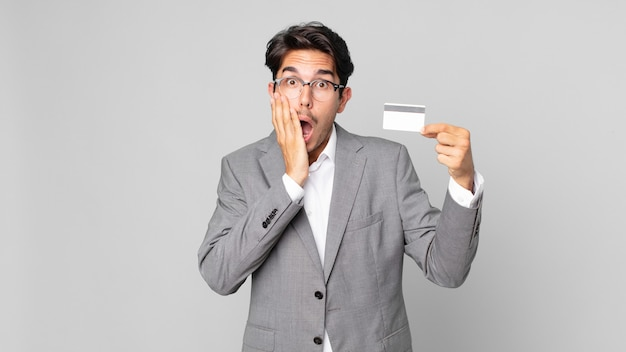 Young hispanic man feeling shocked and scared and holding a credit card