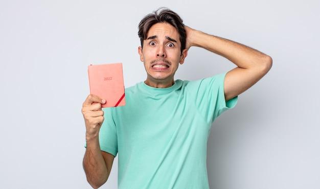Молодой латиноамериканец чувствует стресс, тревогу или страх, с руками за голову. концепция планировщика 2022 года