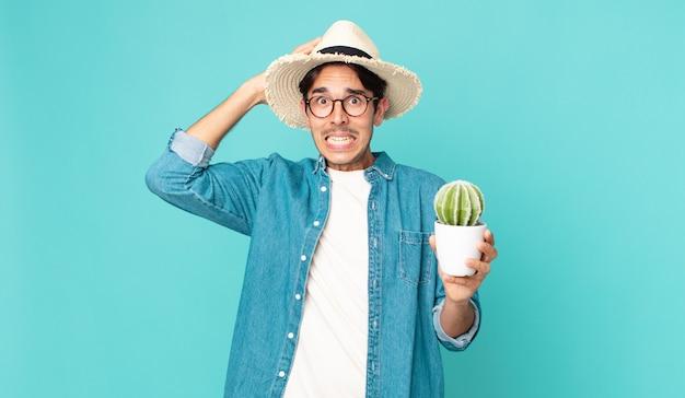頭に手を置き、サボテンを持って、ストレス、不安、または恐怖を感じている若いヒスパニック系男性