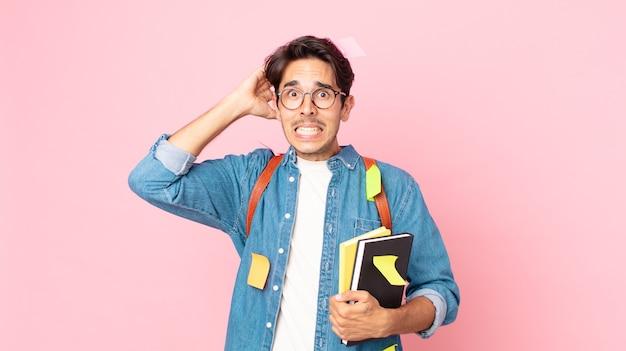 若いヒスパニック系の男性は、頭に手を置いて、ストレス、不安、または恐怖を感じています。学生の概念