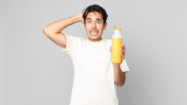 コーヒーの魔法瓶で頭に手を置いて、ストレス、不安、または恐怖を感じている若いヒスパニック系男性
