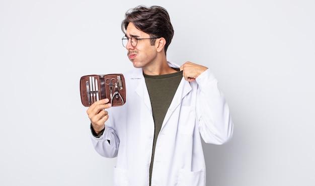 젊은 히스패닉 남자는 스트레스를 받고, 불안하고, 피곤하고, 좌절감을 느낍니다. 척추측만증 손톱 도구