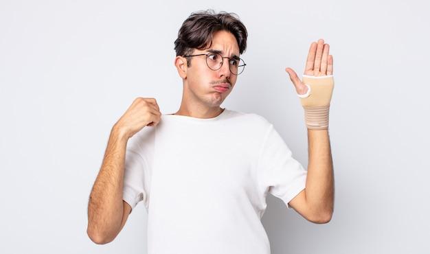 젊은 히스패닉 남자는 스트레스를 받고, 불안하고, 피곤하고, 좌절감을 느낍니다. 손 붕대 개념
