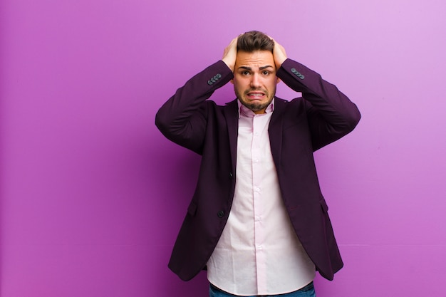 Young hispanic man feeling stressed, worried, anxious or scared, with hands on head, panicking at mistake