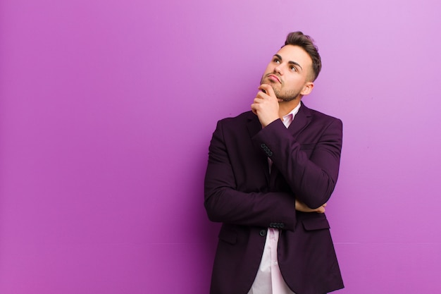 Young hispanic man feeling thoughtful, wondering or imagining ideas, daydreaming and looking up to copyspace