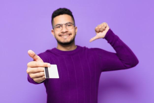 若いヒスパニック系男性の幸せな表現とクレジットカードを保持しています