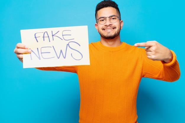 若いヒスパニック系男性の幸せな表現の偽のニュースの概念