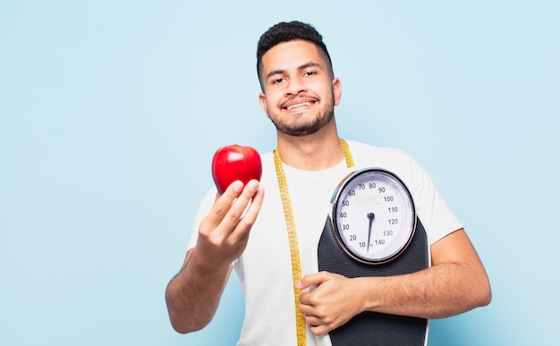 Young hispanic man happy expression and holding an apple. diet concept