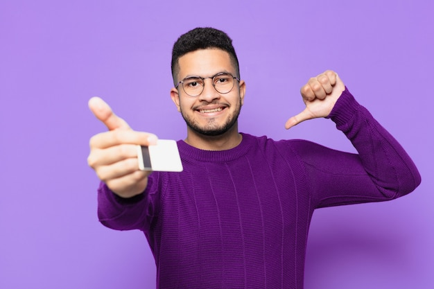 Young hispanic man happy expression and holding a credit card