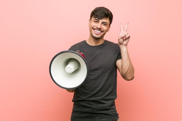 Молодой латиноамериканский мужчина держит мегафон, показывая знак победы и широко улыбается.