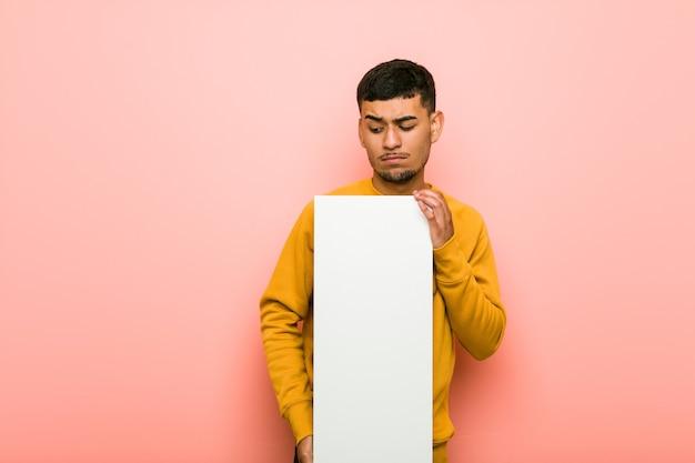 Молодой латиноамериканский мужчина держит плакат