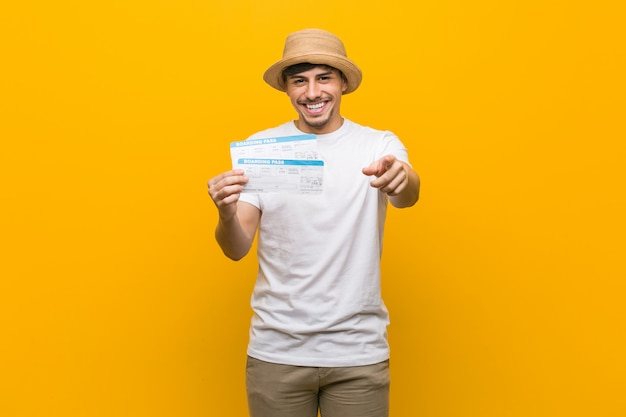 Young hispanic man holding an air tickets cheerful smiles pointing to front.