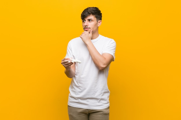 Young hispanic man holding an airplane icon looking sideways with doubtful and skeptical expression.