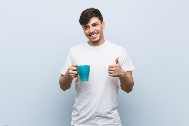 Young hispanic man holding a cup smiling and raising thumb up