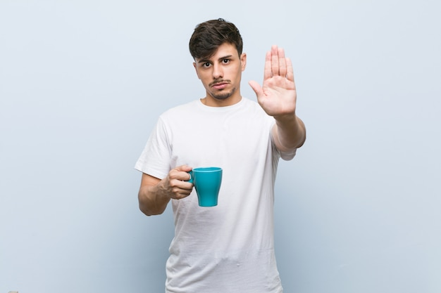 Young hispanic man holding a cup standing with outstretched hand showing stop sign, preventing you.