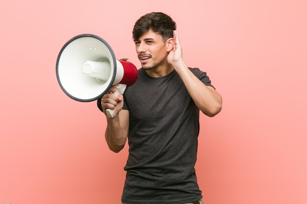 Young hispanic man holding a megaphone trying to listening a gossip.