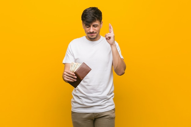 Young hispanic man holding a wallet crossing fingers for having luck