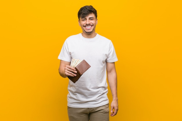 Young hispanic man holding a wallet happy, smiling and cheerful.