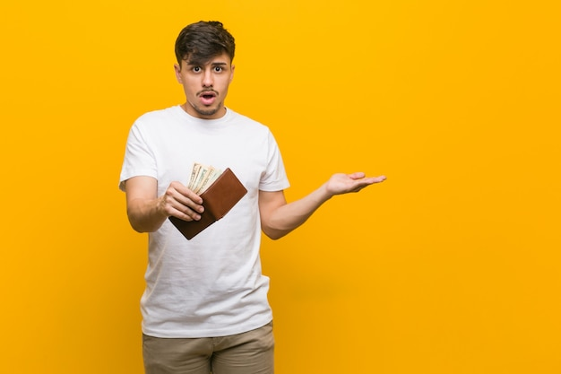 Young hispanic man holding a wallet impressed holding copy space on palm.