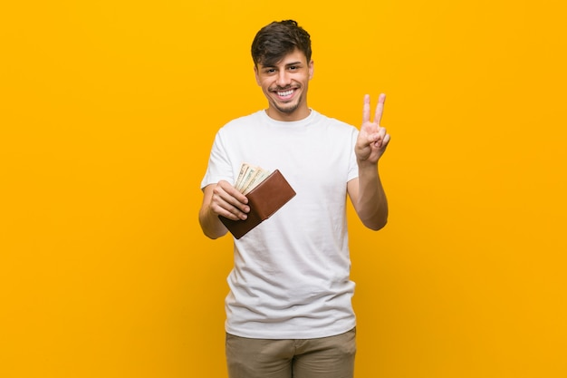 Young hispanic man holding a wallet showing number two with fingers.