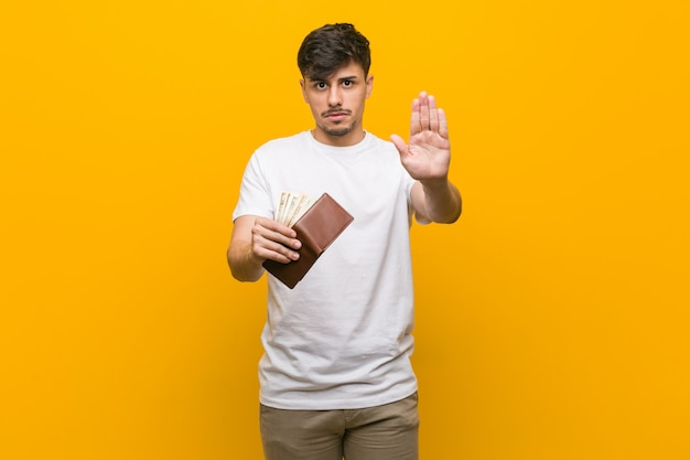 Young hispanic man holding a wallet standing with outstretched hand showing stop sign, preventing you
