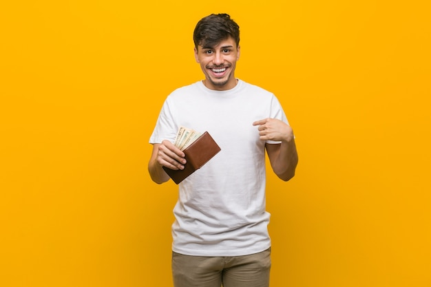 Young hispanic man holding a wallet surprised pointing at himself, smiling broadly.
