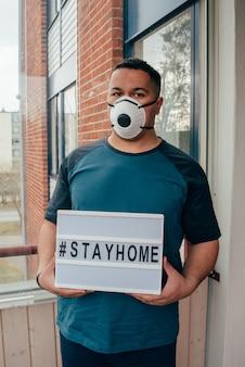 ヒスパニック系の若者がサインを保持する家に滞在