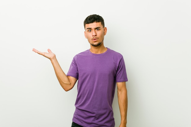 Young hispanic man impressed holding copy space on palm.
