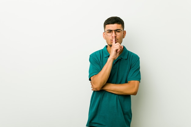 Young hispanic man keeping a secret or asking for silence.