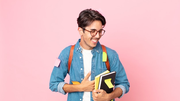 Young hispanic man laughing out loud at some hilarious joke. student concept