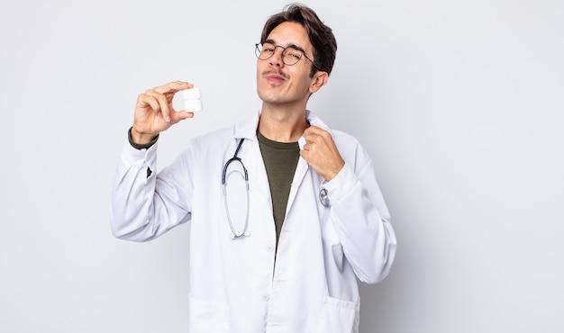 Молодой латиноамериканец выглядит высокомерным, успешным, позитивным и гордым. врач с концепцией бутылки таблетки