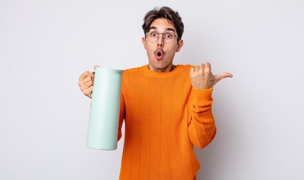 信じられないことに驚いたように見える若いヒスパニック系の男性。魔法瓶のコンセプト