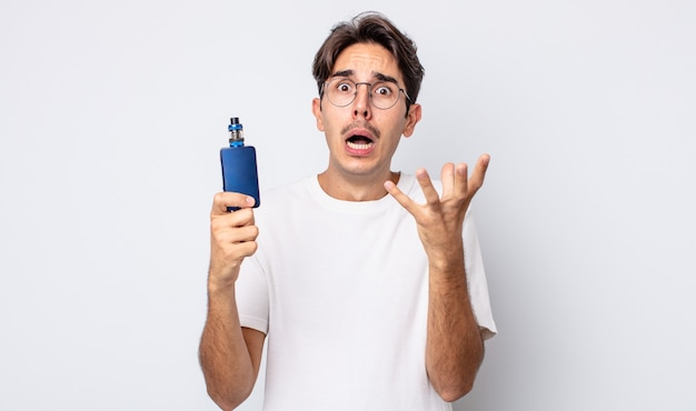 Young hispanic man looking desperate, frustrated and stressed. smoke vaporizer concept