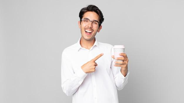 興奮して驚いた若いヒスパニック系の男性が横を指して、テイクアウトのコーヒーを持っています