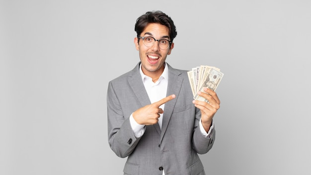 Young hispanic man looking excited and surprised pointing to the side