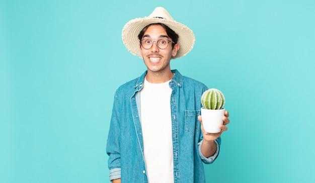 幸せそうに見えて、嬉しそうに驚いて、サボテンを持っている若いヒスパニック系の男性