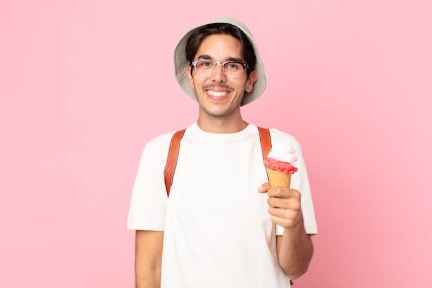 Молодой латиноамериканец выглядит счастливым и приятно удивленным и держит мороженое