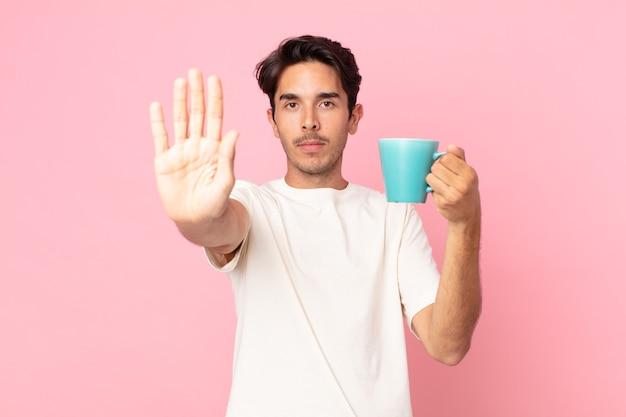 真剣に見える若いヒスパニック系の男性は、開いた手のひらを停止ジェスチャーをし、コーヒーマグを保持していることを示しています