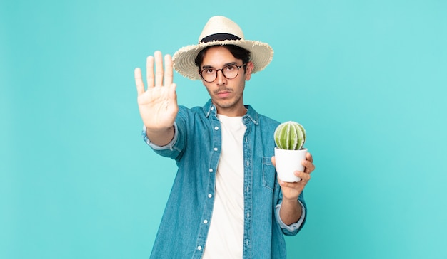 Young hispanic man looking serious showing open palm making stop gesture and holding a cactus
