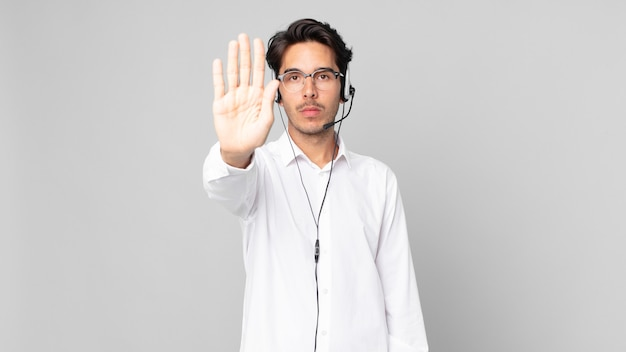 Young hispanic man looking serious showing open palm making stop gesture. telemarketer concept