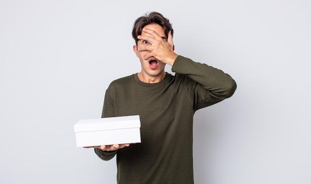 충격, 겁 또는 겁에 질려 보이는 젊은 히스패닉 남자, 손으로 얼굴을 덮고 있습니다. 흰색 상자 개념