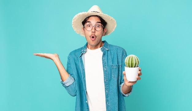 驚いてショックを受けた若いヒスパニック系の男性が、オブジェクトを持ってサボテンを持って顎を落とした